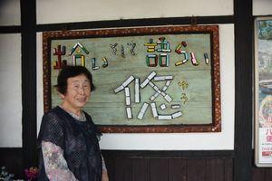 23年にわたって三間坂駅を見守ってきた杉光さん。後ろは駅に掲げられた「悠」の手作りの看板=武雄市山内町の三間坂駅
