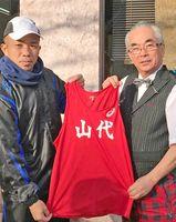 山代町体協チームの貞方聡郁監督(左)にユニホームを贈った松永一広さん