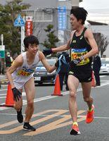 嬉野・太良の1区岡島慶典選手(右)が2区井手孝一選手にたすきを渡す。ともに区間2位でチームの日間3位に貢献した=鳥栖署前