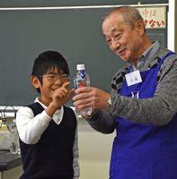 魚型のしょうゆ入れで作った浮沈子の動きを観察する児童=佐賀市の中川副小学校