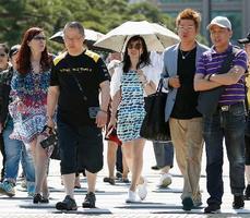 日傘を差して皇居付近を歩く女性ら=25日午前
