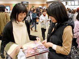 ライブ中継オリジナルパンフレット「朝夏まなとラストデイ」を見るファン=佐賀市の109シネマズ佐賀