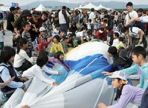 気球教室で力を合わせて球皮を畳む子どもたち=佐賀市の嘉瀬川河川敷