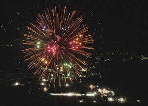 メイン会場の上空で大輪の花を咲かせるカラフルな花火(ドローンで空撮)
