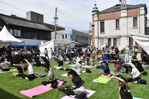 ハナマルシェの会場でヨガを体験する来場者たち=唐津市本町の旧唐津銀行周辺