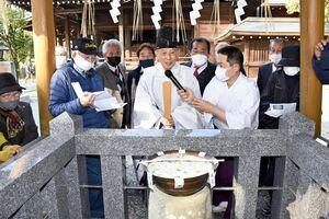 カビが生えたお粥を前に、御粥試しの結果を発表する東正弘宮司(中央)=みやき町の千栗八幡宮