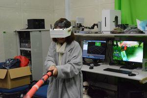 仮想現実とモーションキャプチャーが体験できるゲーム。おもちゃの刀を動かすと画面上の剣も連動する=佐賀市の佐賀大学クリエイティブラーニングセンター