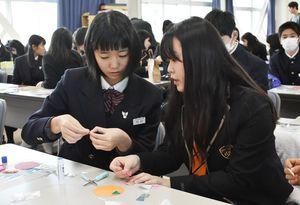 コースター作りで交流を深める両校の生徒たち=佐賀市の佐賀商業高校