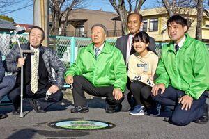 校内に設置されたオリジナルマンホールの前で記念写真に納まる稲冨礼那さん(右から2人目)ら=佐賀市の若楠小