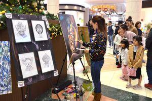 絵を描くアーティストの姿に見入る子どもたち