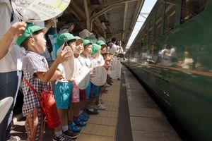 特製うちわを振って「ゆふいんの森」号を出迎える園児たち=鳥栖市のJR鳥栖駅