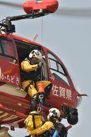 伊万里・有田消防本部の上空で、停止飛行をしたまま要救助者をヘリに収容する航空隊員=伊万里市立花町