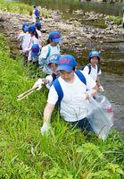 河川敷のごみを拾い集めるリバーフォーラム2100の参加者=有田町の有田川