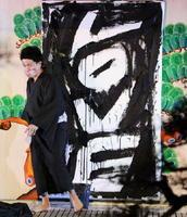 書道家の山口芳水さんが画布を黒く染め、最後に「LOVE」の文字が浮かび上がった=嬉野市の和多屋別荘