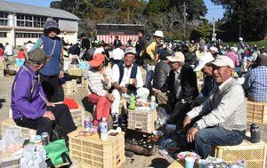 焼き肉を囲んで談笑する人たち=伊万里市大川町の大川運動広場