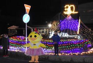 直径約10メートルのロータリーを飾ったイルミネーション。着ぐるみは地元のゆるキャラ「ぴおん」=唐津市肥前町の市民センター前