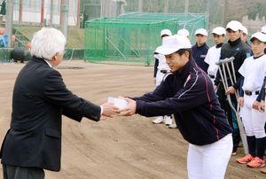 伊万里高野球部の犬塚晃海主将に記念品を贈る原口隆さん=伊万里高グラウンド