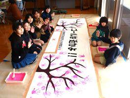 さが桜マラソンのランナーを後押しする応援布を作っている若楠校区の子どもたち=佐賀市の若楠公民館