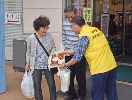 手作りの法被を着て買い物客にチラシを配る民生委員=佐賀市川副町のスーパーモリナガ空港通り店
