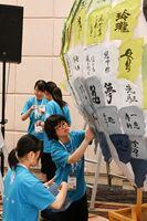 参加者が書いた作品をバルーンの形のオブジェに貼り付ける生徒たち