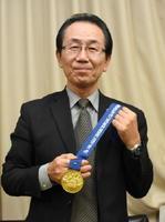 チーム戦優勝の金メダルを手に喜ぶ久保さん=武雄市役所