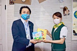 お菓子を手渡す衛藤愛さん(中央)と山田健一郎さん=佐賀市神園のココロ保育園