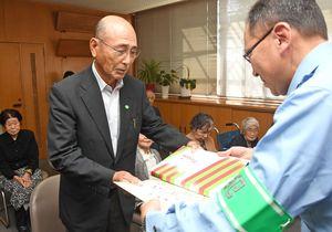 原尚士署長(右)から表彰状と副賞を受け取る山崎一臣さん=神埼市の神埼署