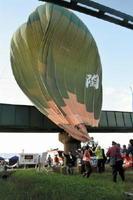 線路に接触し、地上からロープで引っ張られる気球=佐賀市の嘉瀬川河川敷