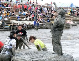 全身泥まみれになりながら、こぶしを突き上げ喜ぶ女子相撲大会優勝者=鹿島市の七浦海浜スポーツ公園