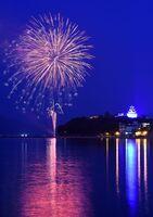 唐津市西の浜にサプライズで打ち上がった花火。右は青くライトアップされた唐津城=1日午後8時、唐津市