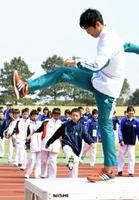青山学院大学陸上競技部の選手(手前)の動きを見ながら、入念にストレッチをする参加者たち=鹿島市陸上競技場