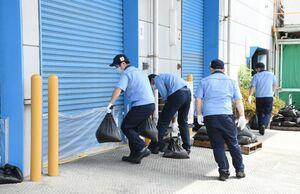 訓練で油槽のある建物のシャッターに止水シートを取り付け、土のうを置く社員=杵島郡大町町の佐賀鉄工所大町工場