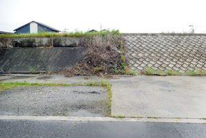かさ上げ工事を終えた堤防(右側)と、古いままの共有地の部分(左側)には、くっきりと境目が=佐賀市の早津江漁港