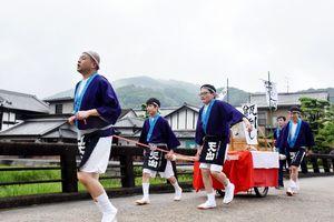 樽を載せたリヤカーを引き、威勢よく酒蔵を出発する天山酒造の社員=小城市小城町