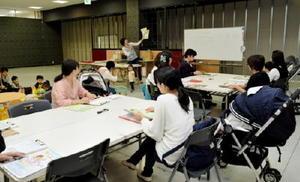 配布資料の確認をする寺野幸子さんと参加者たち=佐賀市のモラージュ佐賀