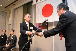 知事賞の表彰状を受ける西村鐵工所の泉章営業本部長(左)=佐賀市のホテルニューオータニ佐賀