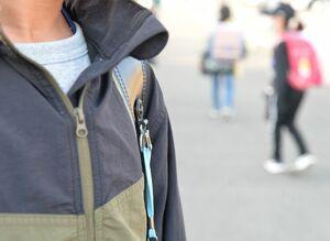 名札を外して登校する小学生。県警からの要請もあり、4月から実施する学校もある