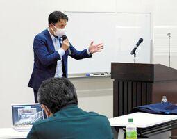 シンポジウムで、佐賀未来創造基金の取り組みを説明する山田健一郎代表理事=佐賀市市民活動プラ