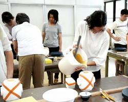 有田焼の製作現場で使われる鋳込み成型を体験する高校生=有田町の佐賀大有田キャンパス