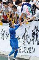 優勝を決め、応援の生徒とハイタッチする神埼の選手=佐賀市の県総合運動場陸上競技場