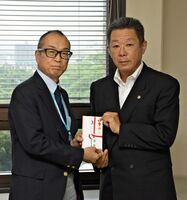 県に寄付金を贈った佐賀ライオンズクラブの小宮清隆会長(右)。左は県健康福祉部の宮原弘行副部長=県庁