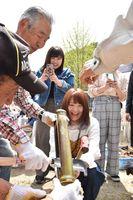 竹筒を割り、炊きあがったご飯を取り出す学生たち=多久市の南部小南渓分校跡