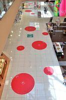 ソーシャル・ディスタンス(社会的距離)を体感してもらうために登場した赤い円形のデザイン。大きい方が直径2メートル、小さい方は直径1メートルとなっている=佐賀市巨勢町のモラージュ佐賀
