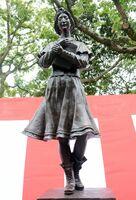 彫刻家諸井謙司さんによるブロンズ像「こころは旅へ」=佐賀市の佐賀県立図書館