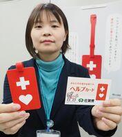 県が配布しているヘルプマーク(左)。右は「手伝ってほしいこと」を裏に書き込み携帯するヘルプカード=佐賀県庁
