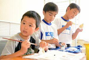 自分の好きな色で人形を塗る児童=神埼市神埼町の西郷小