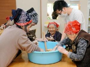 煮た大豆をつぶす作業を夢中で進めるデイサービス宅老所「芽吹き」の利用者ら=嬉野市嬉野町