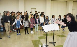 市民合唱団「唐津」を歌う会の合同練習会。右は指揮を務める声楽家の永富啓子さん=10月、唐津市民会館