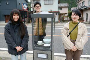 通りのガラスケースに作品を展示している(左から)小早川智里さん鷲見夏樹さん、中村美月さん=有田町の佐賀大有田キャンパス近く