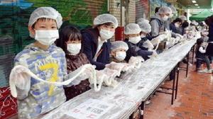 出来上がった長さ60メートル以上の細長い餅を持ち上げ、記録達成を祝う参加者たち=基山町の基山モール商店街